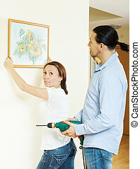 couple choosing place for picture  at home interior