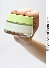 woman hand with cream pot - woman hand holding a container...