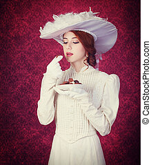 Beautiful redhead women with candy. Photo in retro style...
