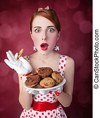 Beautiful redhead women with coockie Photo in retro style...