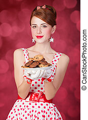 Beautiful redhead women with coockie. Photo in retro style...