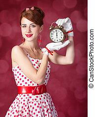 Beautiful redhead women with clock. Photo in retro style...