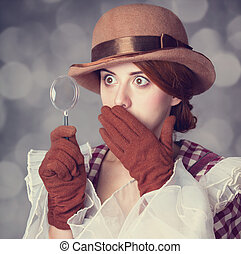 Beautiful redhead women with magnifying glass Photo in retro...