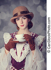 Beautiful redhead women with cup of tea. Photo in retro...