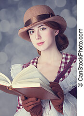 Beautiful redhead women with book. Photo in retro style with...