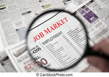 Job Market - Magnifying glass over a newspaper classified...