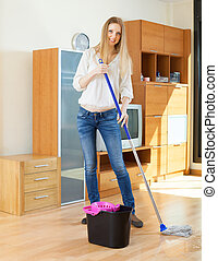ordinary long-haired girl washing floor with mop - ordinary...