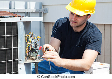 Air Conditioning Repair - Young repairman fixing an...