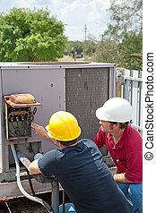 Air Conditioning Repair - Teamwork - Two AC technicians on a...