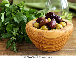 marinated green and black olives Kalamata in a wooden bowl