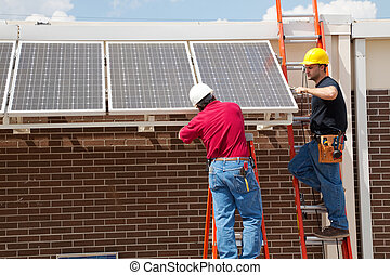 Installing Solar Panels - Two electricians installing solar...