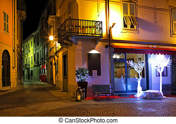 Small restaurant on the corner at night in Italy. - Small...