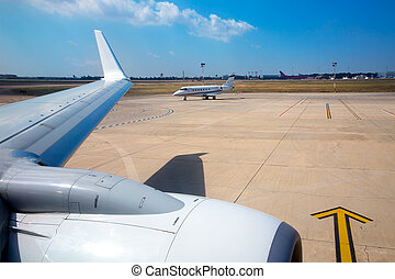 Airplane wing in airport with aircraft background