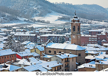 Small town covered with snow in Piedmont, Italy. - Roofs of...