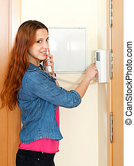 Young beautiful woman using house videophone indoor - Young...