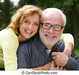 Portrait of a happy husband and wife smiling outdoors -...
