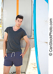 Male fashion model standing outdoors with surfboards