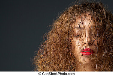 Portrait of a female fashion model with hair and eyes closed