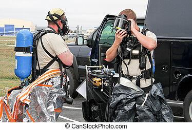 Army Hazmat suit prep - soldiers preparing suits for...