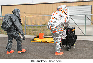men approaching hazmat site - fully suited hazmat...