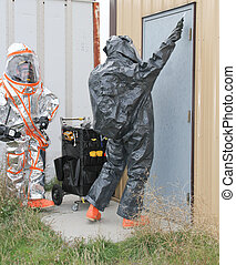 men testing hazmat site door - fully suited hazmat team...