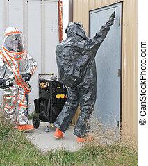 men testing hazmat site door - fully suited hazmat team...