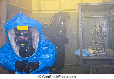 Hazmat team in smoking building - Hazmat team in full gear...