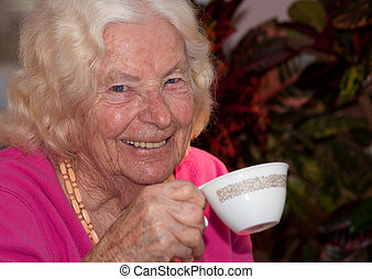 Tea time - Closeup of an elderly woman smiling as she drinks...