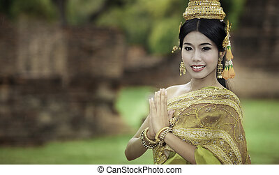 woman performing typical thai dance with thai style temple...