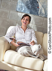 woman reading magazine at home - happpy young woman reading...