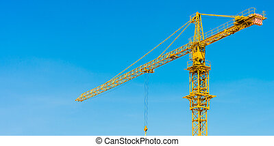 hoisting crane and blue sky - yellow hoisting crane with...