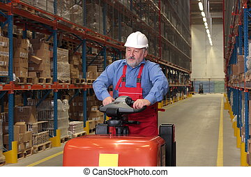 A senior worker driving the fork lift through a storage room...