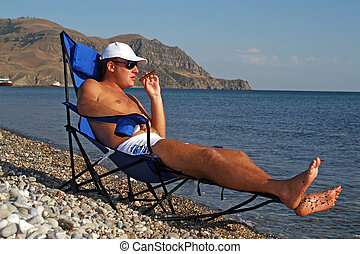 The young man in sunglasses with a cigar has a rest on seacoast