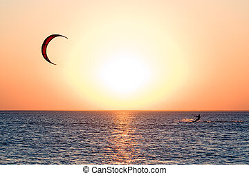 Kitesurfer on a gulf on a sunset