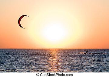Kitesurfer on a gulf on a sunset