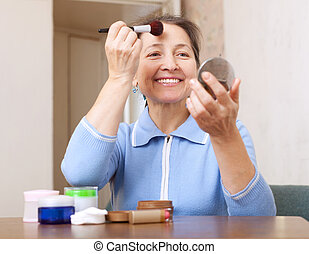 mature woman putting facepowder - Smiling mature woman...
