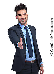 smiling business man is welcoming you with a hand shake -...
