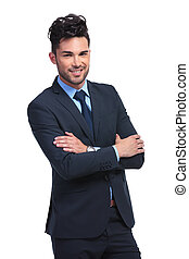 smiling young business man standing with arms folded
