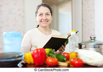 mature housewife reads cookbook for recipe - Happy mature...