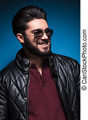 side of a young man with nice hairstyle and beard smiling -...