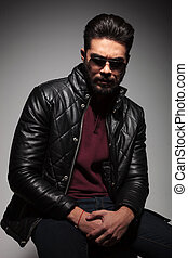 dramatic shot of a young man with beard in leather jacket...