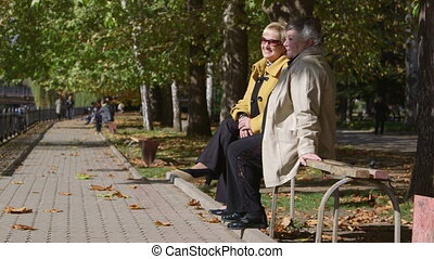 Two senior women talking on park bench