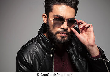 man with long beard fixing or putting on his sunglasses -...