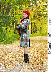 mature woman walking in autumn - Happy mature woman in coat...