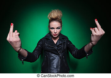 young woman in leather jacket is flipping you off on a green...