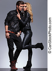 couple dressed in leather clothes in a fashion pose - in...