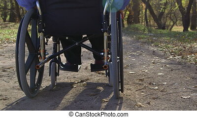 Senior woman in a wheelchair - Disabled senior woman turning...