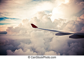 Clouds and sky as seen through window of an aircraft at...