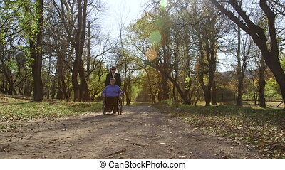 woman in wheelchair - Caregiver pushing wheelchair with...