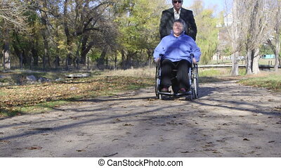 disabled senior in wheelchair - Caregiver man walking with...